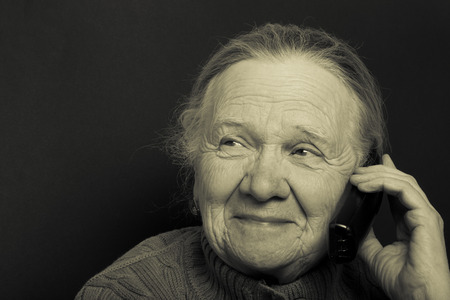 grayness: Portrait of elderly woman with telephone on dark background. Toned. Stock Photo