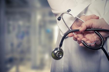De dokter legde zijn handen met een stethoscoop op zijn rug op een onscherpe achtergrond. Afgezwakt.