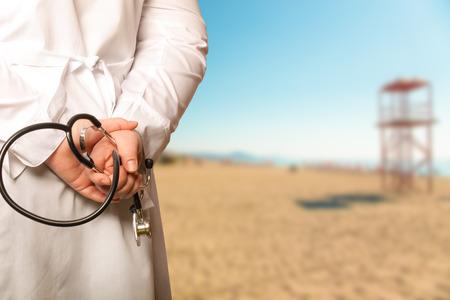 Der Arzt legte seine Hände mit Stethoskop auf dem Rücken auf einem unscharfen Hintergrund. Getontes.
