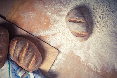 milling rolling: Fresh home bread fell in a heap of flour. Toned. Stock Photo