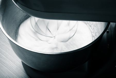 albumin: The process of whipping egg whites in a planetary mixer. Selective focus. Toned. Stock Photo