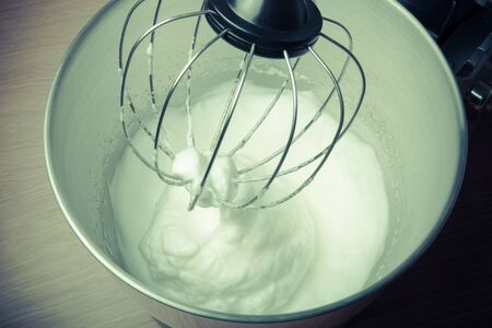 planetary: The process of whipping egg whites in a planetary mixer. Toned. Stock Photo
