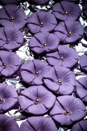 fondant fancy: Many sugar mastic flowers for background. Toned.