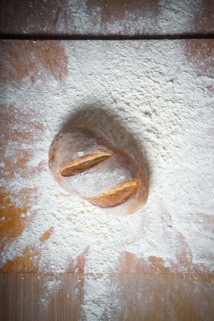 Fresh home bread fell in a heap of flour. Toned. Stock Photo