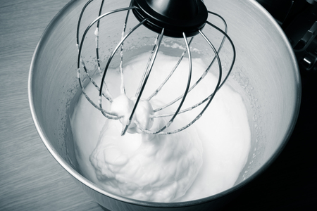 albumin: The process of whipping egg whites in a planetary mixer. Toned. Stock Photo