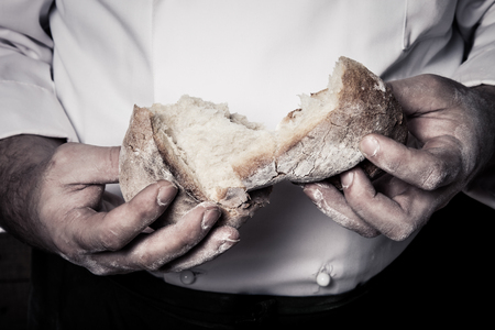 Fresh home bread in male's hands. Toned.