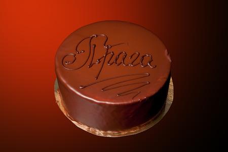 praga: Chocolate cake with inscription Praga on colored background. Stock Photo