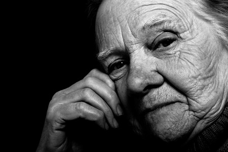 grayness: Portrait of elderly woman on dark background. Toned.