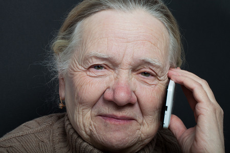 grayness: Portrait of elderly woman with telephone on dark background. Stock Photo