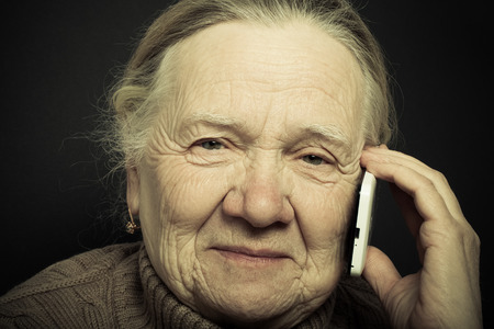 Portrait of elderly woman with telephone on dark background. Toned. Stock Photo