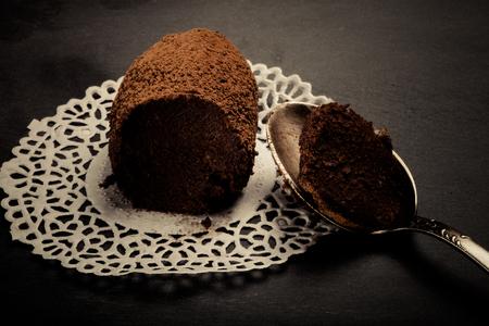 rum cake: Fresh homemade chocolate cake Kartoshka  on tracery paper substrate. Toned.