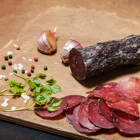 cutting horse: Sliced horse sausage, herbs and spices on cutting board. Selective focus. Shallow depth of field.