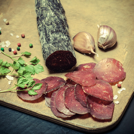 cutting horse: Sliced horse sausage, herbs and spices on cutting board. Selective focus. Shallow depth of field. Toned.