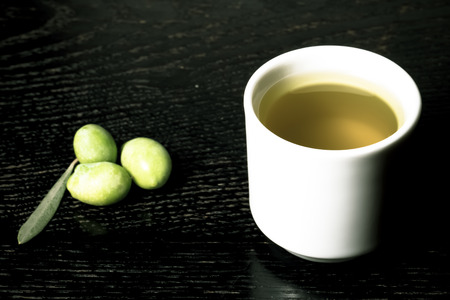 olive green: Green olive berries and cap of fresh olive oil on a black wooden table or board. Toned. Stock Photo