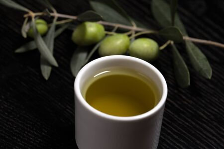 olive green: Branch of olive tree with green olive berries and cap of fresh olive oil on a black wooden table or board. Selective focus.