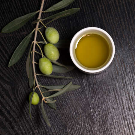 olive green: Branch of olive tree with green olive berries and cap of fresh olive oil on a black wooden table or board. Stock Photo