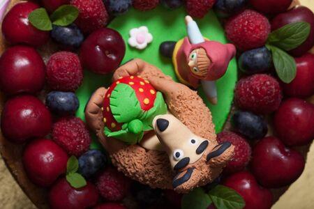 homemade cake: Homemade cake with mastic figures and berries.