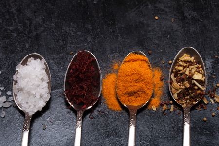 karri: Old metal spoons with different kind of spices on a black background.