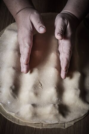 cut up: Female hands cut up dough. Toned.