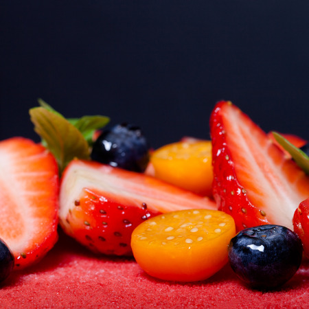 three layer: Many fresh berries on bright mousse cake. Selective focus. Shallow depth of field. Toned.