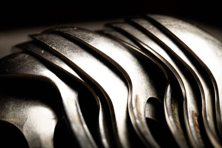 grunge flatware: Lot of metal cutlery on a black background. Selective focus. Shallow depth of field. Toned.