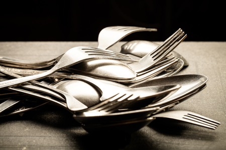 grunge cutlery: Lot of metal cutlery on a black background. Selective focus. Shallow depth of field. Toned.