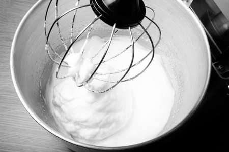 planetary: The process of whipping egg whites in a planetary mixer. Selective focus. Toned. Stock Photo