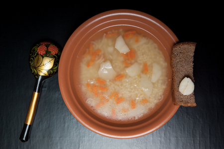 Rice soup in a clay plate on a black table or background. Toned.