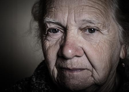 grayness: Portrait of an elderly woman. Closeup view. Toned.