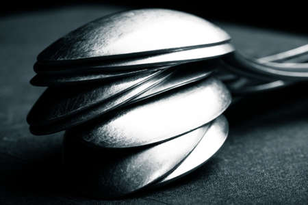 grunge silverware: Lot of metal cutlery on a black background. Selective focus. Shallow depth of field. Toned.