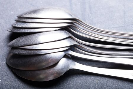 grunge flatware: Lot of metal cutlery on a black background. Selective focus. Shallow depth of field.