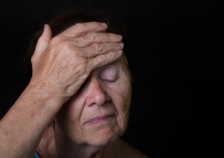 grayness: Portrait of elderly woman. Closes eyes with hands. Stock Photo