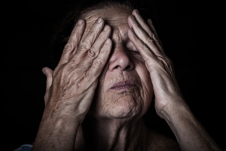 closes eyes: Portrait of elderly woman. Closes eyes with hands. Toned.