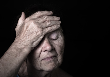 Portrait of elderly woman. Closes eyes with hands. Toned.
