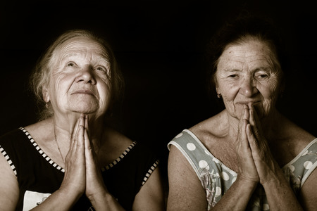 Portrait of two elderly sisters. Prayer. Toned.