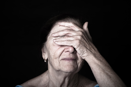 grayness: Portrait of elderly woman Closes eyes with hands. Toned.