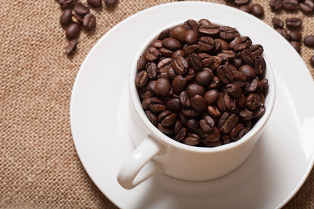 Coffee beans and coffee in cup on burlap. Selective focus. Stock Photo