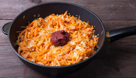 Chopped carrots and onions with tomatoes paste in a frying pan fried in oil.