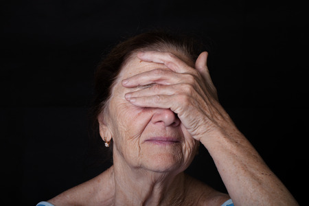 closes eyes: Portrait of elderly woman. Closes eyes with hands. Stock Photo