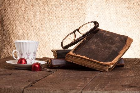 Tasse Kaffee, shokolad, Gläser und Stapel alte Bücher auf dem alten Holztisch.