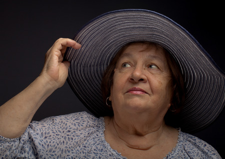 grayness: Portrait of an elderly woman in a hat with the fields. Toned.