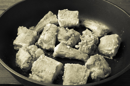 fishery products: Fried fish fillet on a frying pan. Toned. Stock Photo