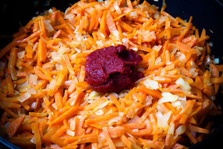 Chopped carrots and onions with tomatoes paste in a frying pan fried in oil. Toned.