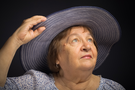 Portrait of an elderly woman in a hat with the fields. Toned.