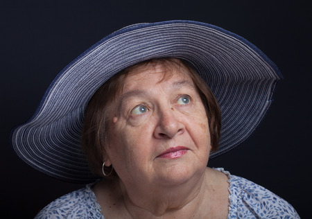 Portrait of an elderly woman in a hat with the fields.
