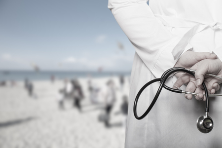 The doctor put his hands with stethoscope behind his back on a blurred background. Toned.