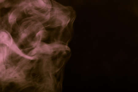 weightless: Cloud of smoke on black background. Selective focus. Toned.