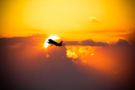 Black silhouette of an airplane on a background of a beautiful sunset. Toned.