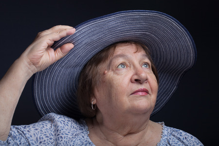 grayness: Portrait of an elderly woman in a hat with the fields.