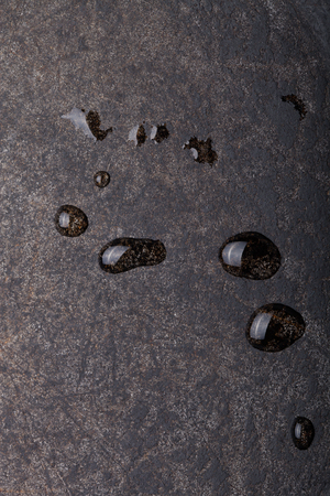 kitchen scraps: Drops of water on black metal background. The surface of the pan to the oven.